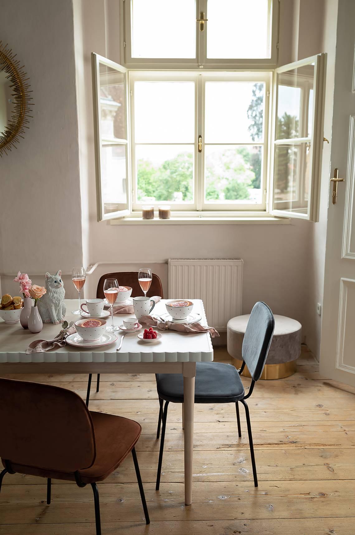 Herzerl gedeckter Tisch umgeben von Stühlen