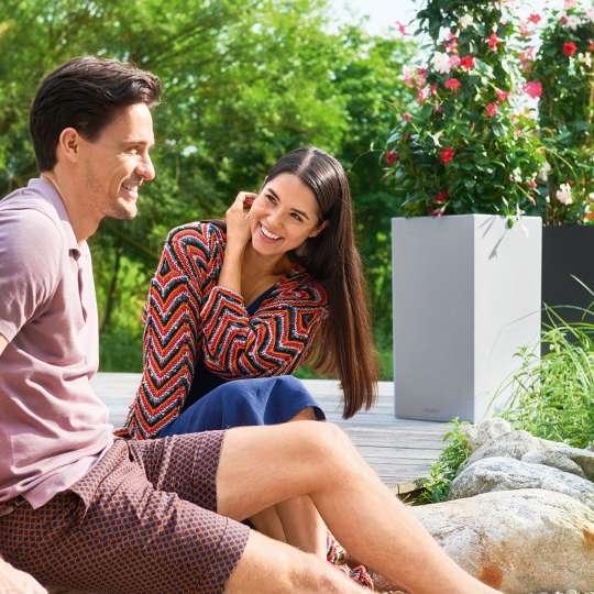 Paar auf Terrasse vor Blumenkübel Canto
